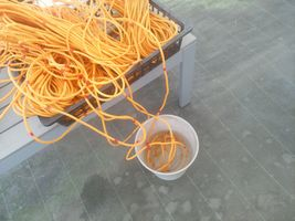 【写真】色々なテープで印をつけた定植用ロープを水を張ったバケツにつけて検証している様子